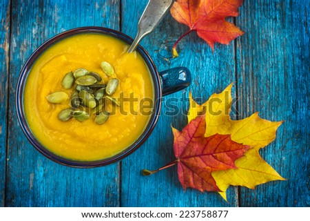 pumpkin soup on a bowl on a blue wooden background, top view - stock photo