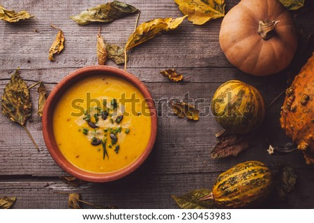 Pumpkin soup on a wooden table - stock photo