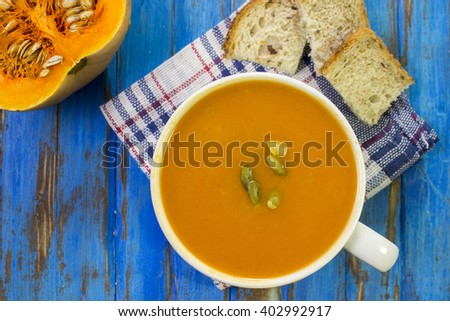 Pumpkin soup puree. Raw pumpkin, slices of bread, blue wooden table. - stock photo