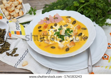Pumpkin soup. Puree soup. Food style. Pumpkin soup puree with seeds, bacon and croutons on wooden table with parsley. - stock photo
