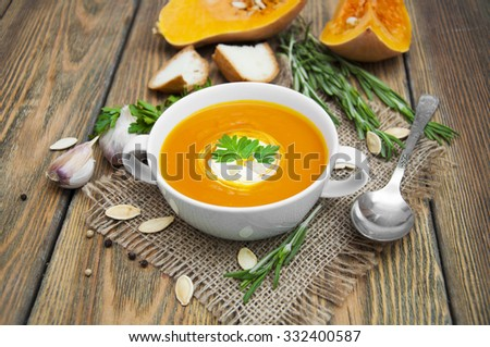 Pumpkin soup puree with spices on a wooden table - stock photo