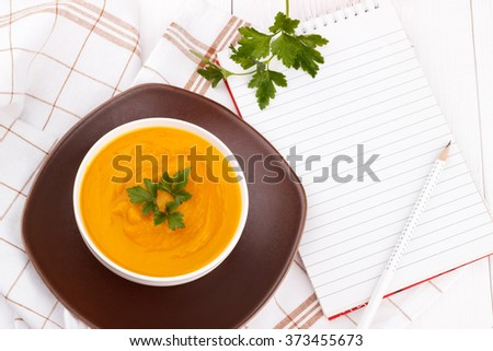 Pumpkin soup with blank recipe book and pencil on white wooden table - stock photo