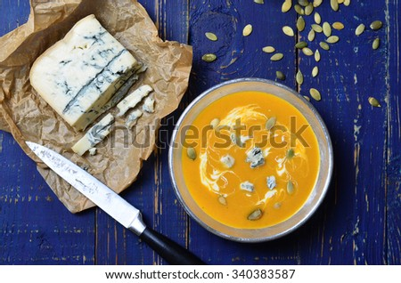 Pumpkin Soup with blue cheese and pumpkin seeds, horizontal, selective focus - stock photo
