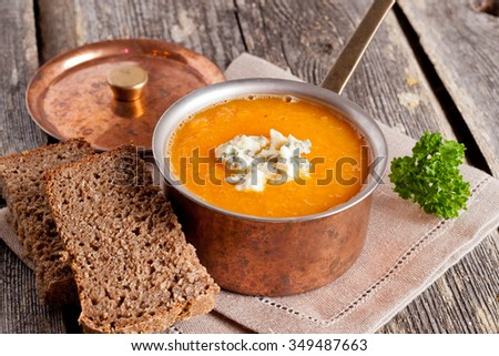 pumpkin soup with blue cheese in a copper pot on a wooden table, close up, horizontal - stock photo