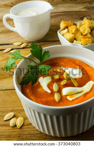 Pumpkin soup with cream, pumpkin seeds in the white bowl, cream in creamer, croutons in serving dish, wooden background close up vertical. Pumpkin soup. Squash soup. Soup. Creamy soup. Vegetable soup  - stock photo