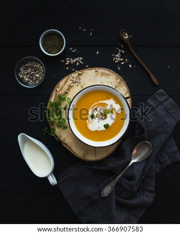 Pumpkin soup with cream, seeds and spices in rustic metal bowl over grunge black background. Top view - stock photo