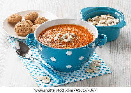 Pumpkin soup with seeds and cookies in blue bowl on wooden background/Pumpkin soup   - stock photo
