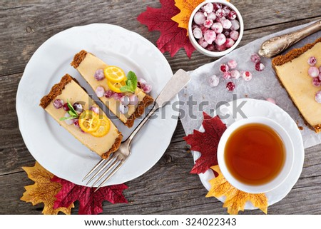 Pumpkin tart on gingerbread crust with candied cranberry - stock photo