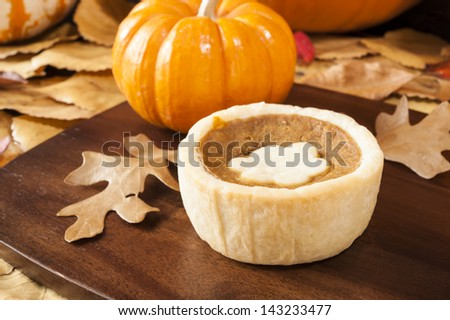 Pumpkin tart surrounded by colorful fall leaves and pumpkins - stock photo