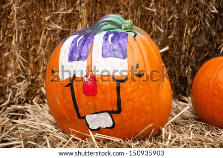 Pumpkin with a painted face. - stock photo