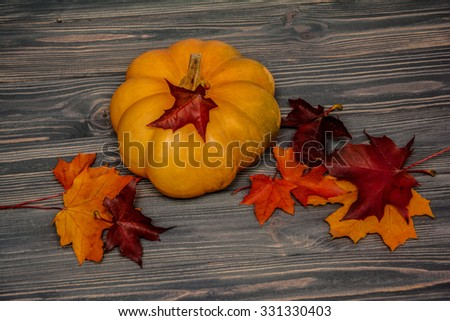 Pumpkin with maple leaves on wooden background. Autumn card - stock photo