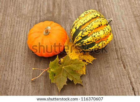 pumpkins and autumn foliage on a wooden table - stock photo