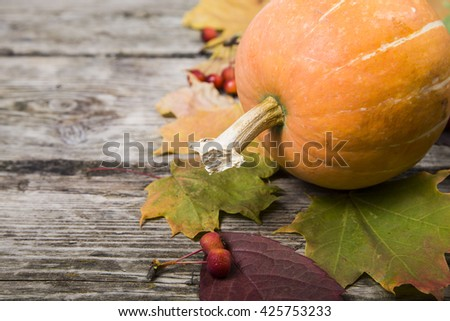 Pumpkins and fall leaves on an old wooden table  - stock photo