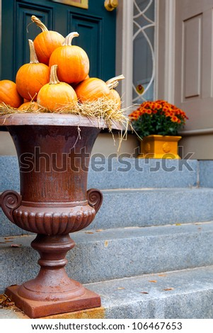 Pumpkins arranged in a large urn by the front door.  Seasonal display for fall. - stock photo