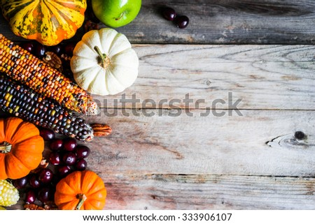 Pumpkins,corn,apples,nuts and cranberries on wooden background - stock photo
