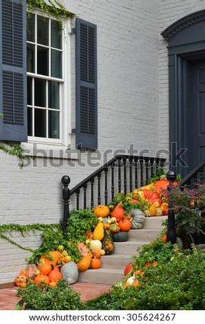 Pumpkins in front door to celebrate Thanksgiving and Halloween  - stock photo