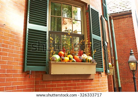 Pumpkins near house window during Halloween season - stock photo