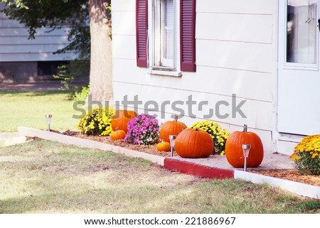 Pumpkins on front steps of home during Halloween/Thanksgiving season  - stock photo