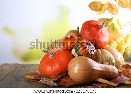 Pumpkins on wooden table on green branch background - stock photo