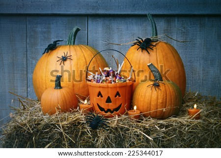 Pumpkins, spiders and Halloween candy on straw - stock photo