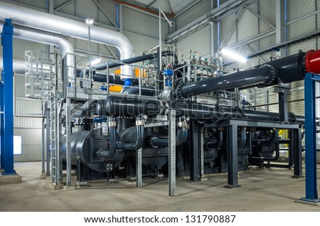 pumps and piping system inside of industrial plant - stock photo