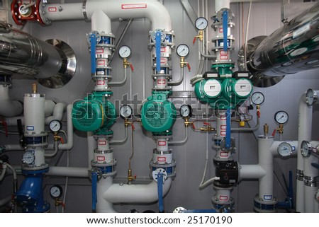 Pumps, pipelines and devices in an interior of modern boiler-house - stock photo