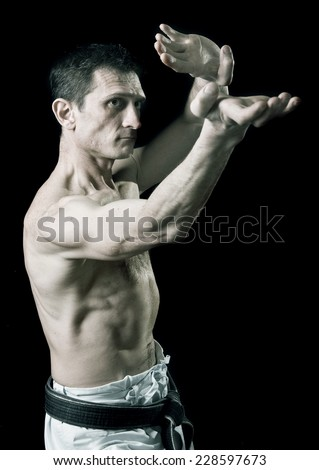 punch.figure in the karate fighting stance on a black background.hand-to-hand fighting.sport.Black-and-white image - stock photo