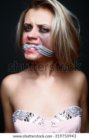 punished woman with rope in mouth  - stock photo