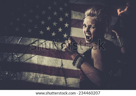 Punk girl against USA flag with brass knuckles and Molotov cocktail  - stock photo