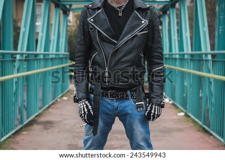 Punk guy with cigarette posing in the city streets - stock photo