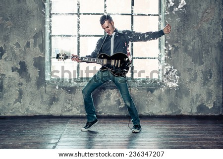 punk rock artist playing guitar in a studio and breaking the window with sound - stock photo