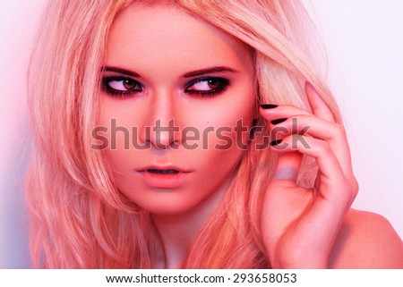 Punk rock style or halloween make-up. Fashion woman model face with bright glamour makeup. Perfect skin, black gloss eyeshadows on eyes and dark brown glossy lips visage. Portrait in red light - stock photo