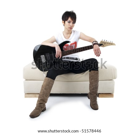 Punk Rockstar holding guitar sitting on sofa isolated in white - stock photo