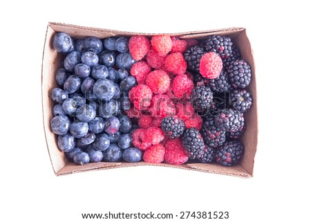 Punnet of ripe assorted fresh autumn berries with blueberries, raspberries and blackberries neatly arranged and viewed from overhead isolated on white - stock photo