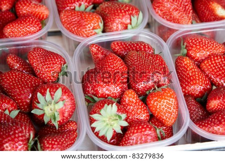 Punnets of strawberries for sale in an outdoor market - stock photo
