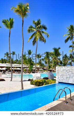 Punta Cana, Dominican Republic - March 25, 2010: Hotel Catalonia Royal Bavaro, Beach hotel resort swimming pool surrounded by palm trees. - stock photo