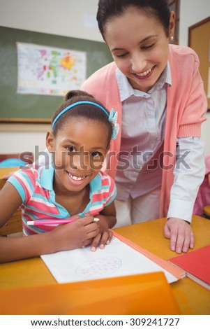 Pupil and teacher at desk in classroom at the elementary school - stock photo