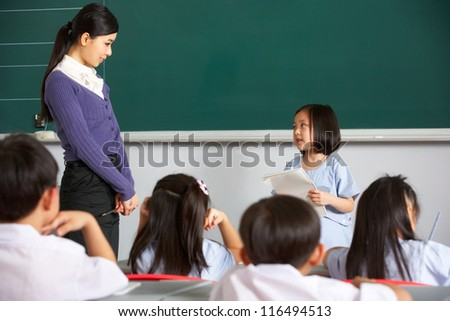 Pupil And Teacher Standing By Blackboard In Chinese School Classroom - stock photo
