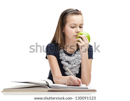 Pupil is eating a ripe apple while studying, isolated, white background - stock photo