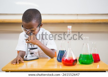 Pupil looking through microscope at the elementary school - stock photo