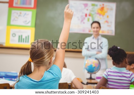 Pupil raising hand in classroom at the elementary school - stock photo