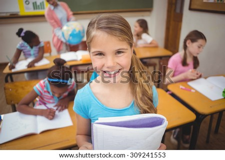 Pupil showing her work to camera at the elementary school - stock photo