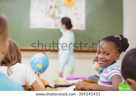 Pupil smiling at camera during class at the elementary school - stock photo
