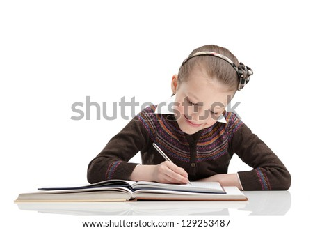 Pupil writes something at her copybook, isolated, white background - stock photo