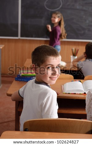 Pupils aged 11 sitting at the desks in classroom - stock photo