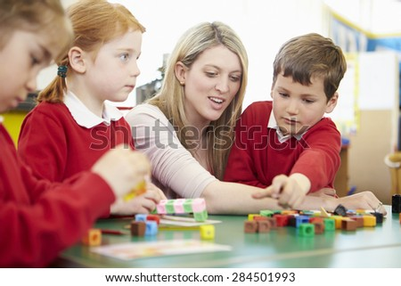 Pupils And Teacher Working With Coloured Blocks - stock photo
