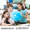Pupils find something at the school globe - stock photo