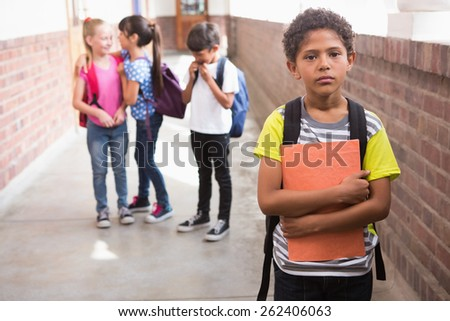 Pupils friends teasing a pupil alone in elementary school - stock photo