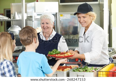 Pupils In School Cafeteria Being Served Lunch By Dinner Ladies - stock photo