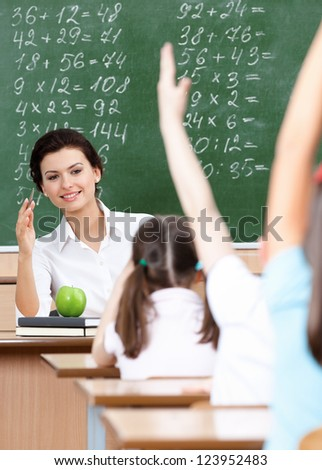 Pupils put their hands up to answer at math - stock photo